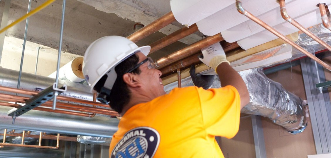 Insulator installing Fiberglass Pipe Insulation